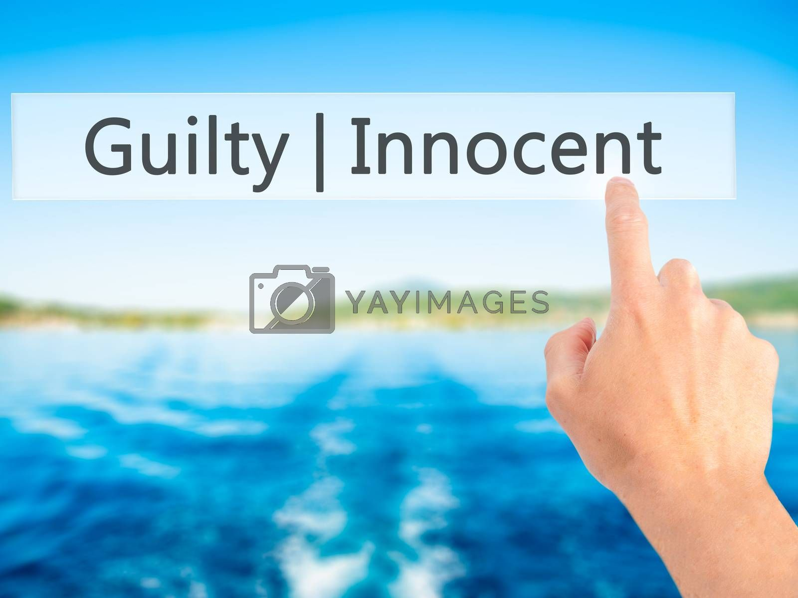 Guilty Innocent - Hand pressing a button on blurred background c by netsay.net