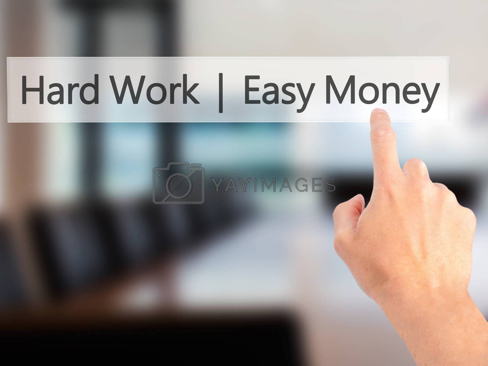 Hard Work  Easy Money - Hand pressing a button on blurred backgr by jackald
