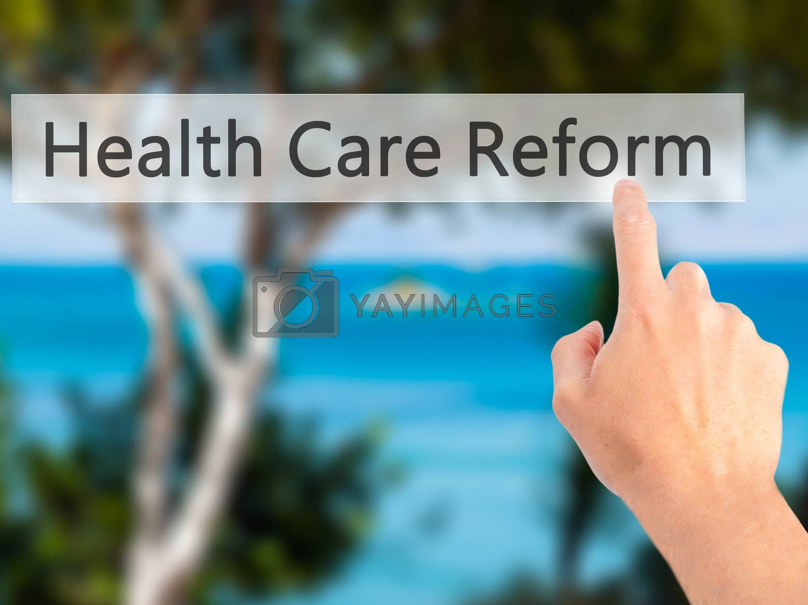 Health Care Reform - Hand pressing a button on blurred backgroun by netsay.net