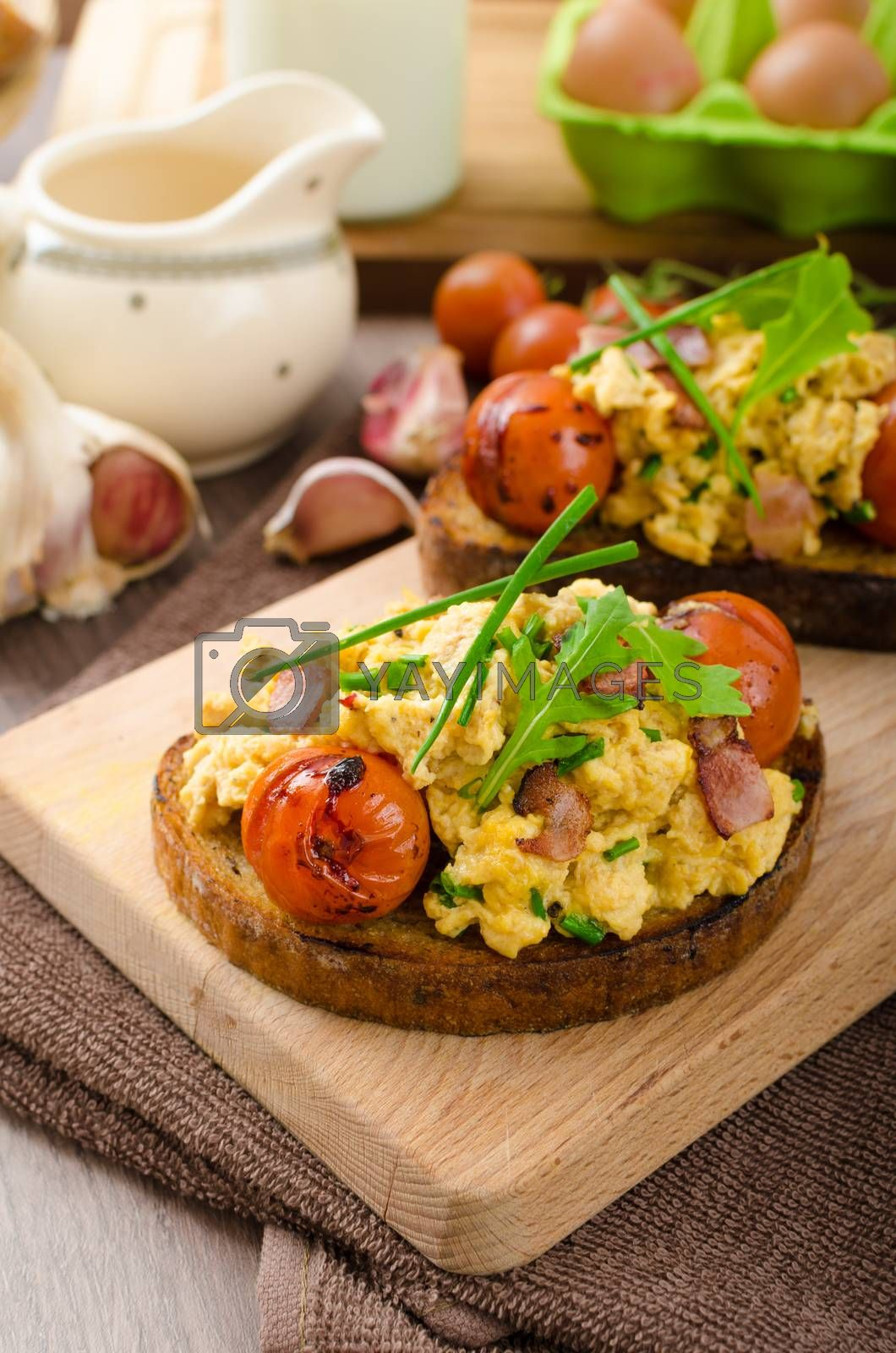 Scrambled eggs on toasted bread with bacon, herbs and tomato poached in balsamic reduction