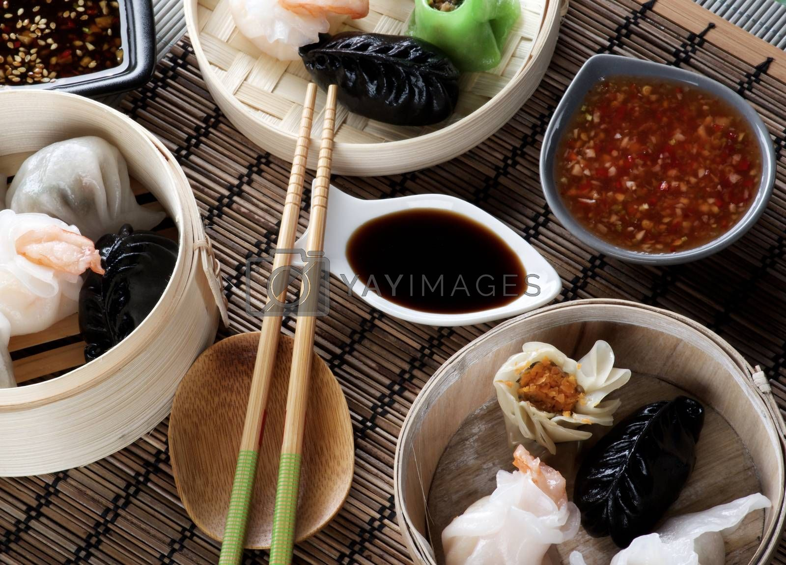 Various Dim Sum in Bamboo Steamed Bowls, Chili and Soy Sauces with Chopsticks closeup on Straw Mat background