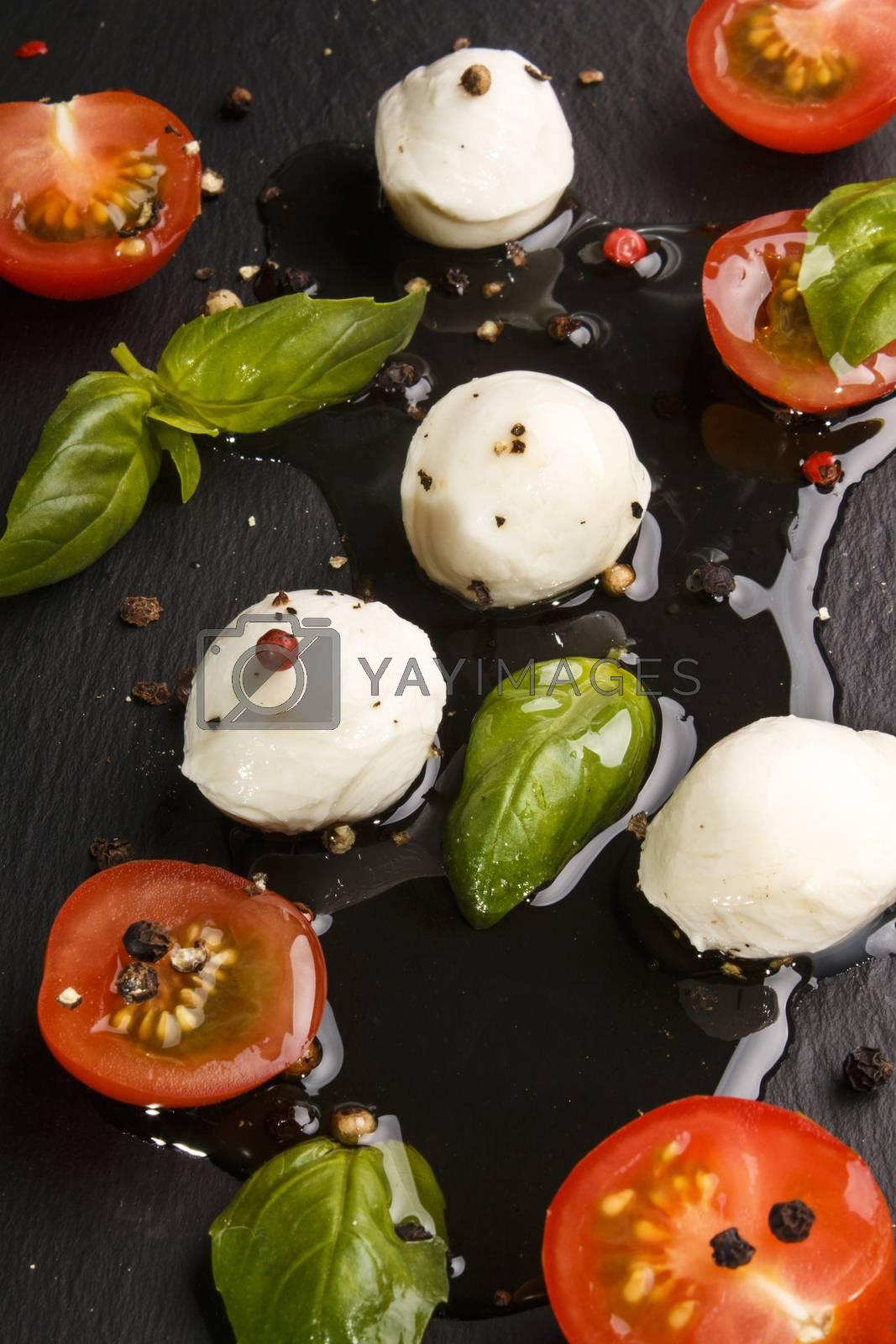 mediterranean salad with cherry tomato, fresh basil, mozzarella and olive oil on slate