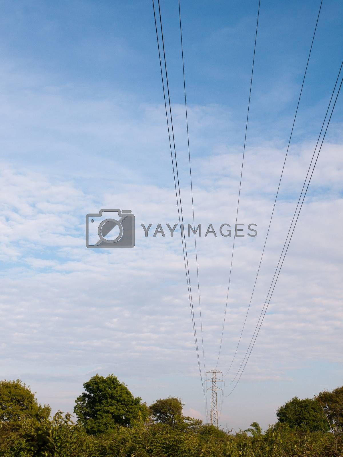 electric wires on a pylon in the distance spreading across the clear blue and cloudy sky beautiful communication peace
