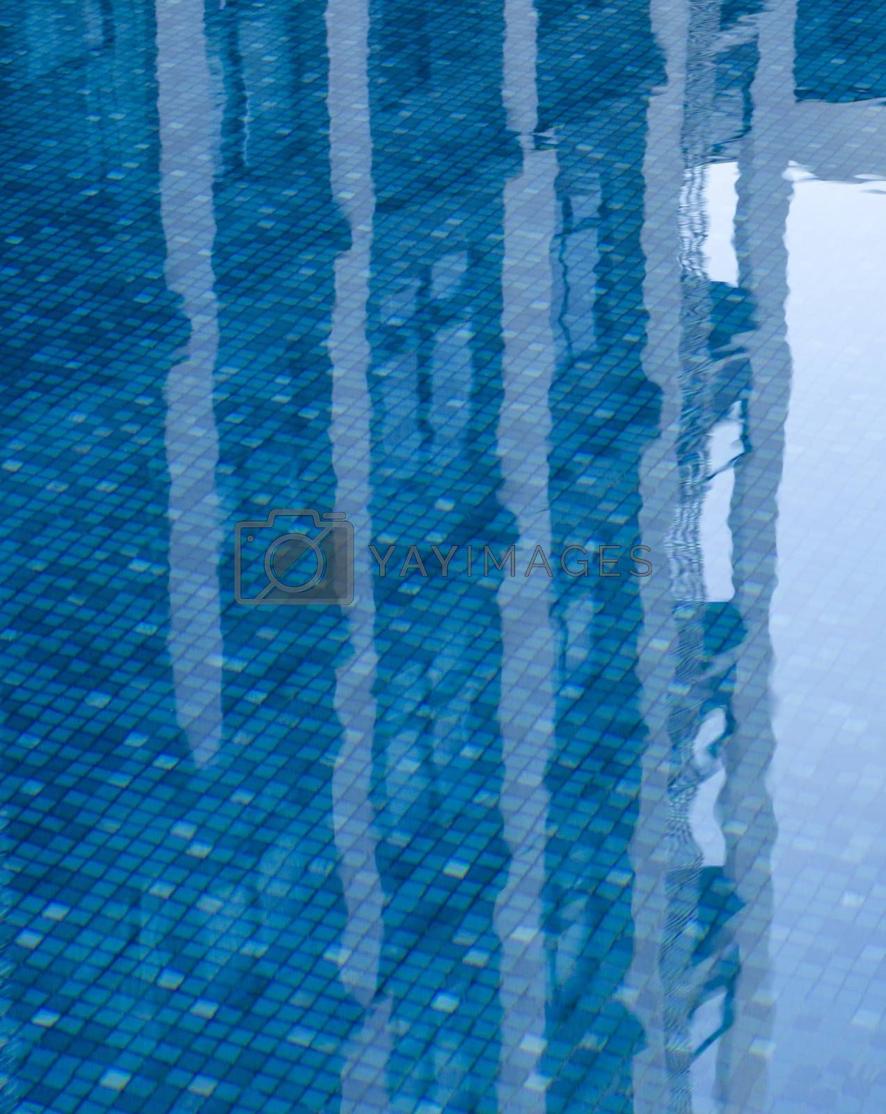 Reflections of building in the calm blue water of a swimming pool
