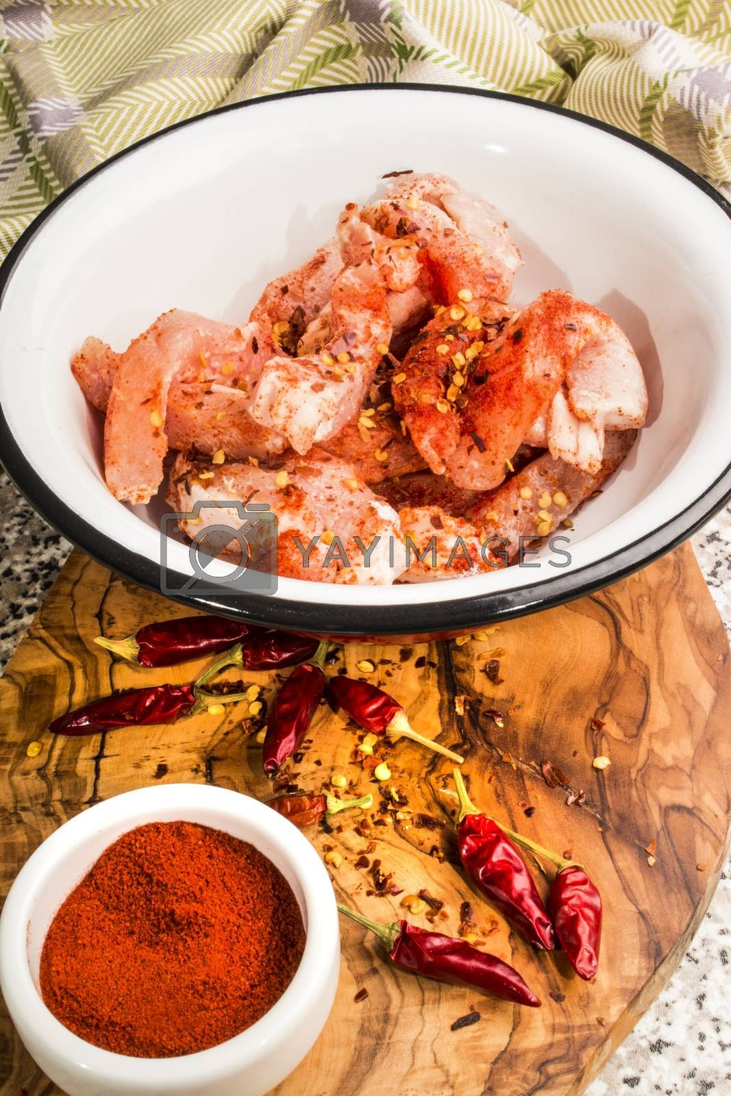 raw pork stripes well coated with flour,  paprika powder and crushed chili flakes in an enamel bowl
