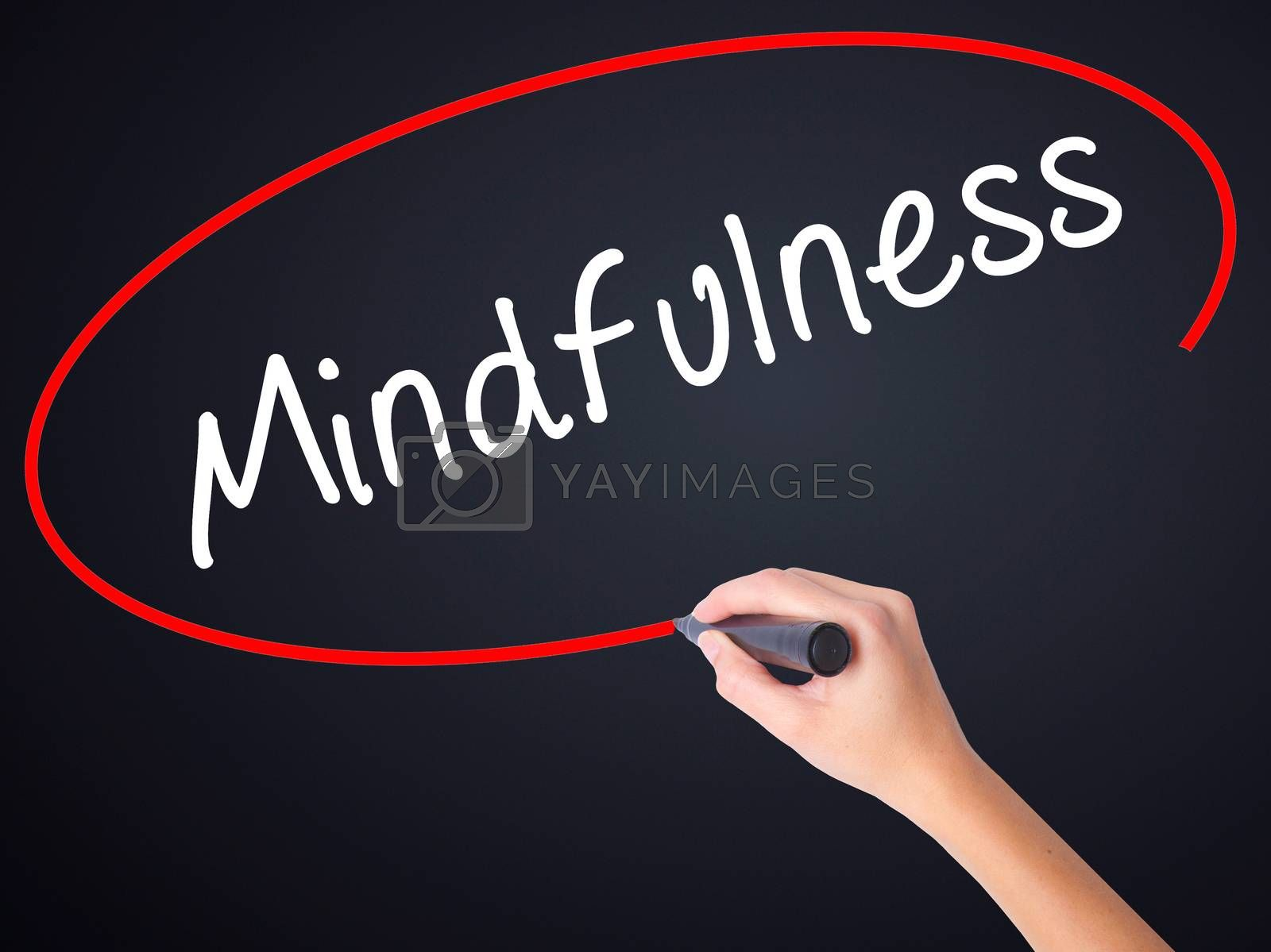 Woman Hand Writing Mindfulness  on blank transparent board with a marker isolated over black background. Business concept. Stock Photo
