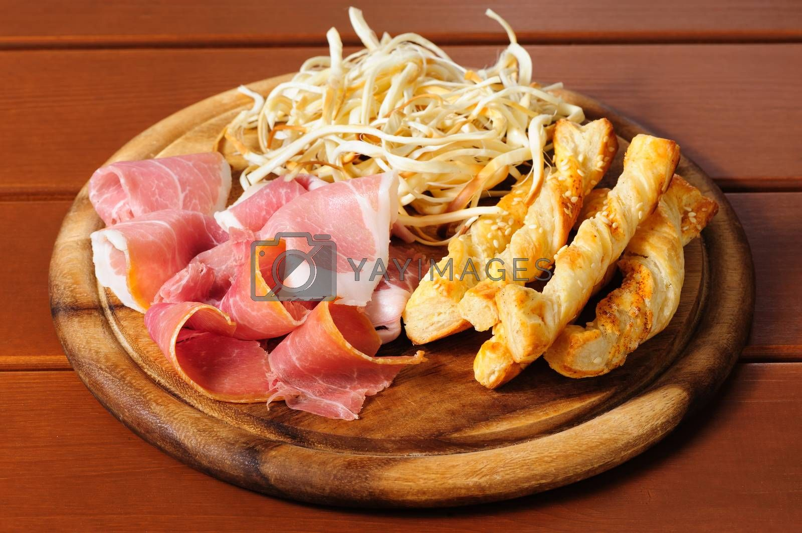 Assorted cold beer snacks on a round wooden board. Dried squid, prosciutto crudo and salted crisps