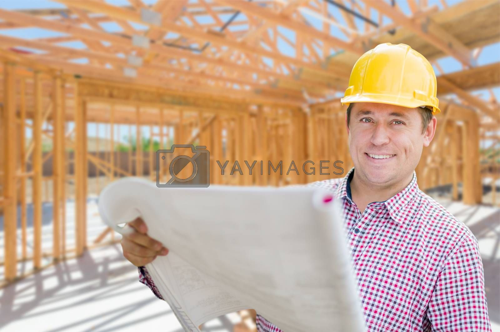 Contractor With Plans On Site Inside New Home Construction Framing. by Feverpitched