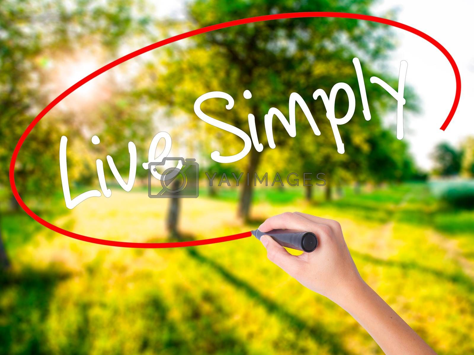 Woman Hand Writing Live Simply on blank transparent board with a marker isolated over green field background. Stock Photo