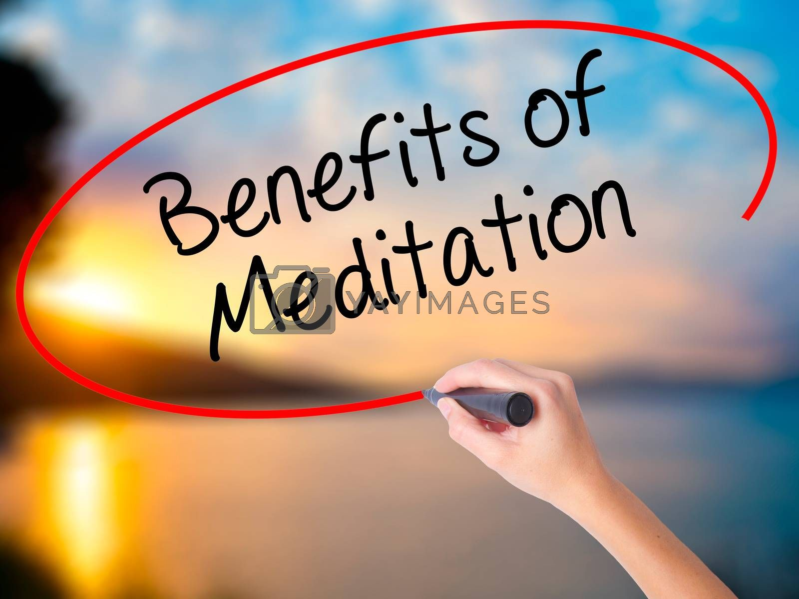 Women Hand writing Benefits of Meditation with black marker on visual screen. Isolated on Sunset. Business, technology, internet concept. Stock Photo