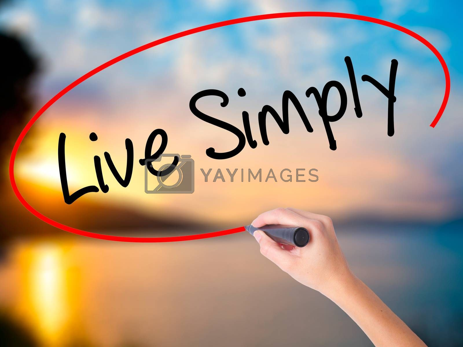 Women Hand writing Live Simply with black marker on visual screen. Isolated on Sunset. Business, technology, internet concept. Stock Photo