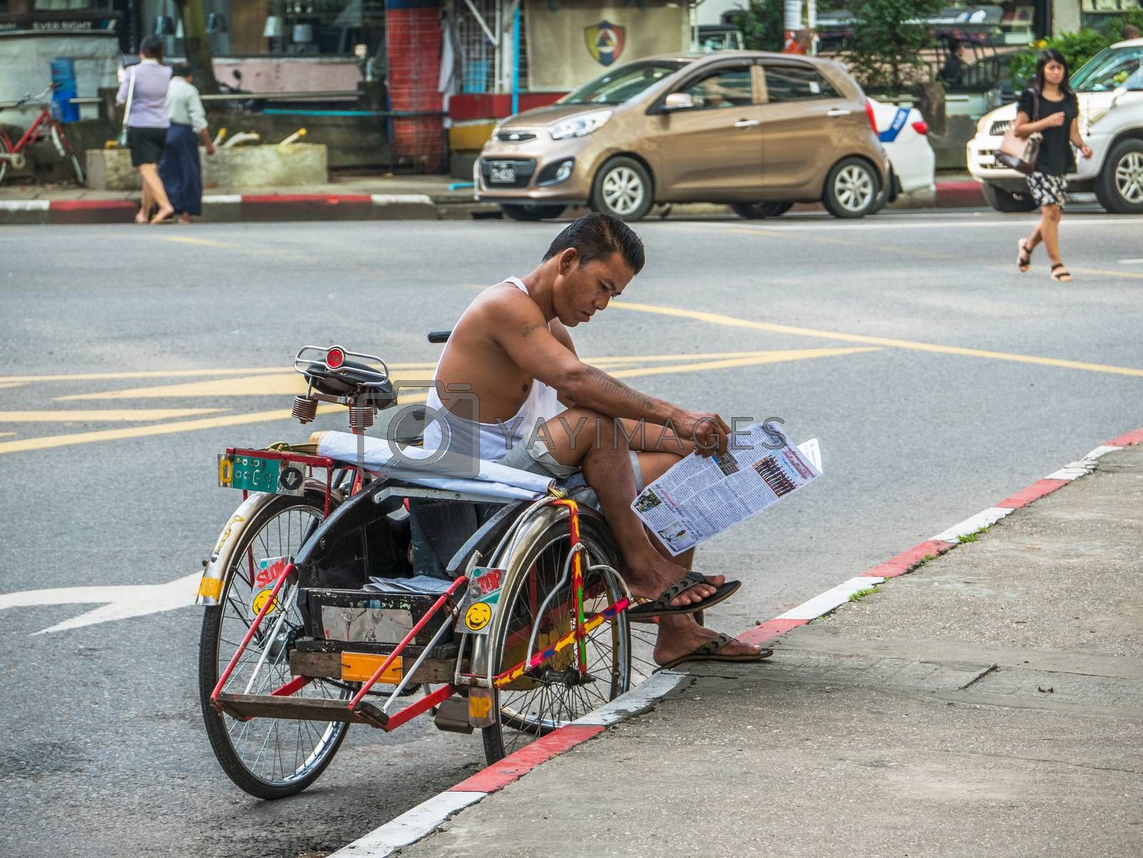 Yangon - September 9, 2016: Tricycle taxis are still common and a practical way of transportation in Myanmar's capital Yangon. Here's a taxi driver who is reading a newspaper while waiting for customers.