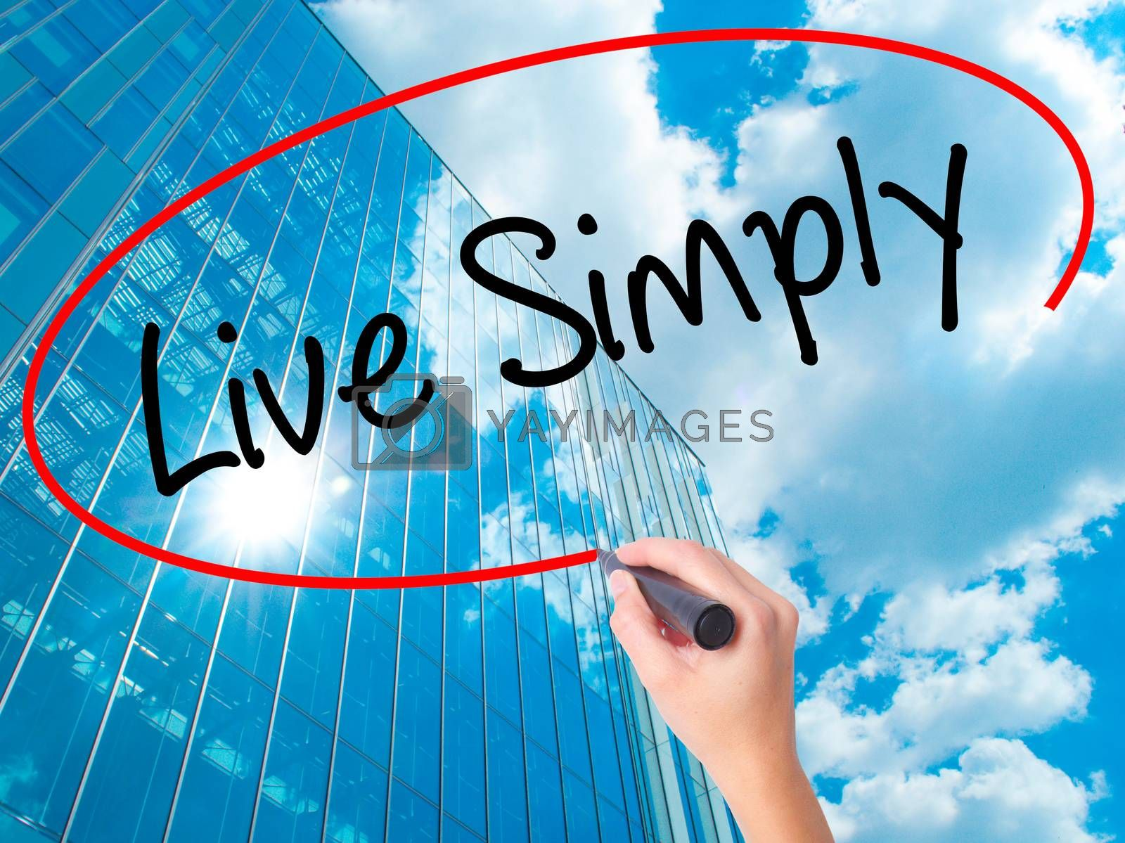 Women Hand writing Live Simply with black marker on visual screen. Isolated on skyscraper. Business, technology, internet concept. Stock Photo