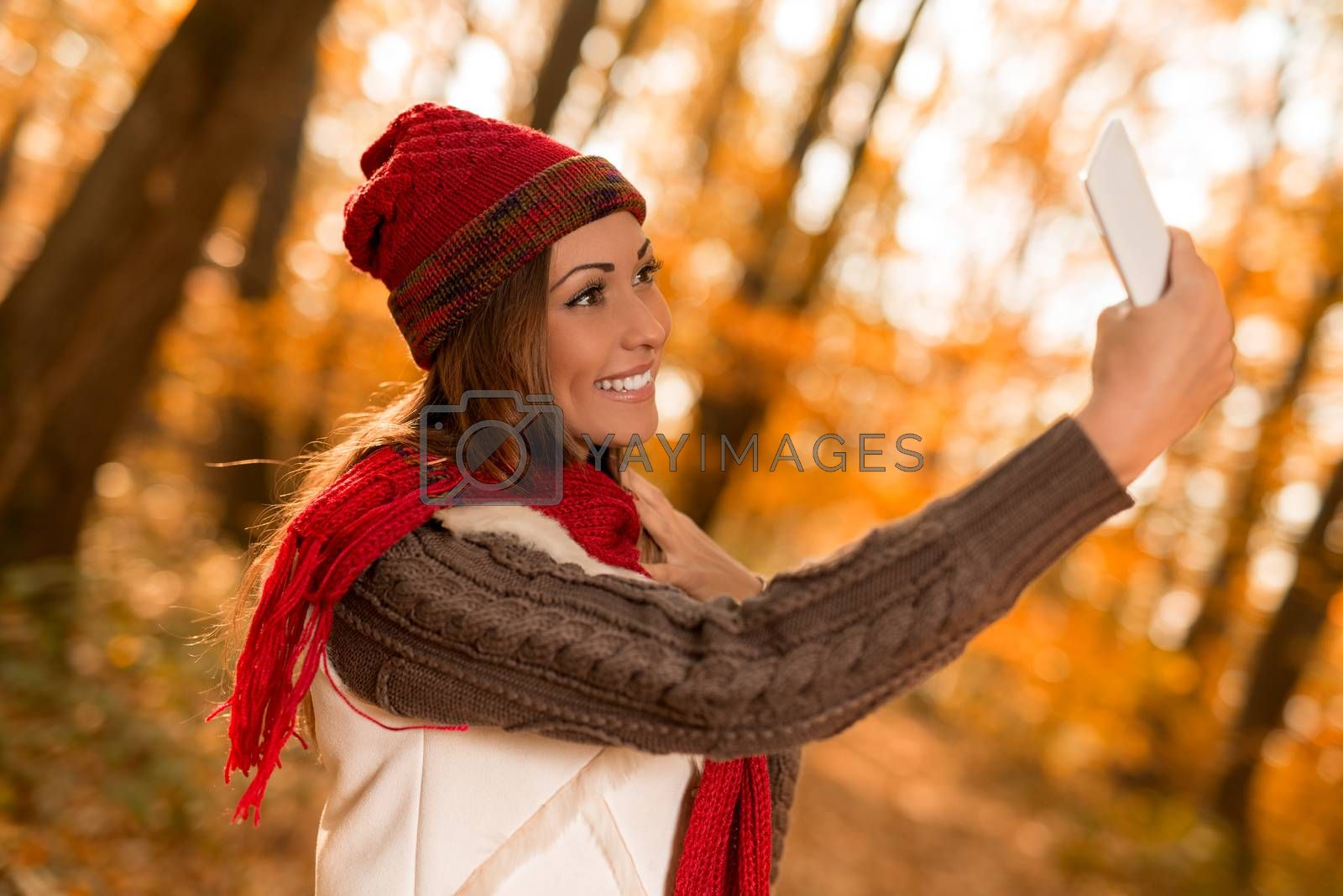 Portrait of a beautiful smiling woman taking selfie in forest in autumn.