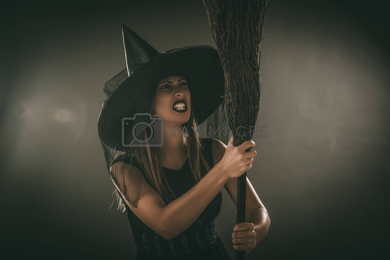 Young woman dressed like a witch. She is in dark clothing and holding a broom.