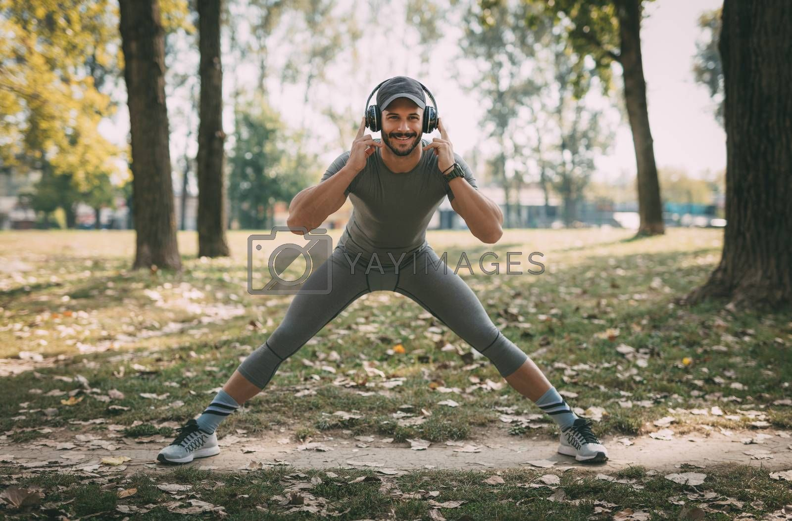 Young smiling sportsman with headphones doing stretching exercise in nature. Looking at camera.