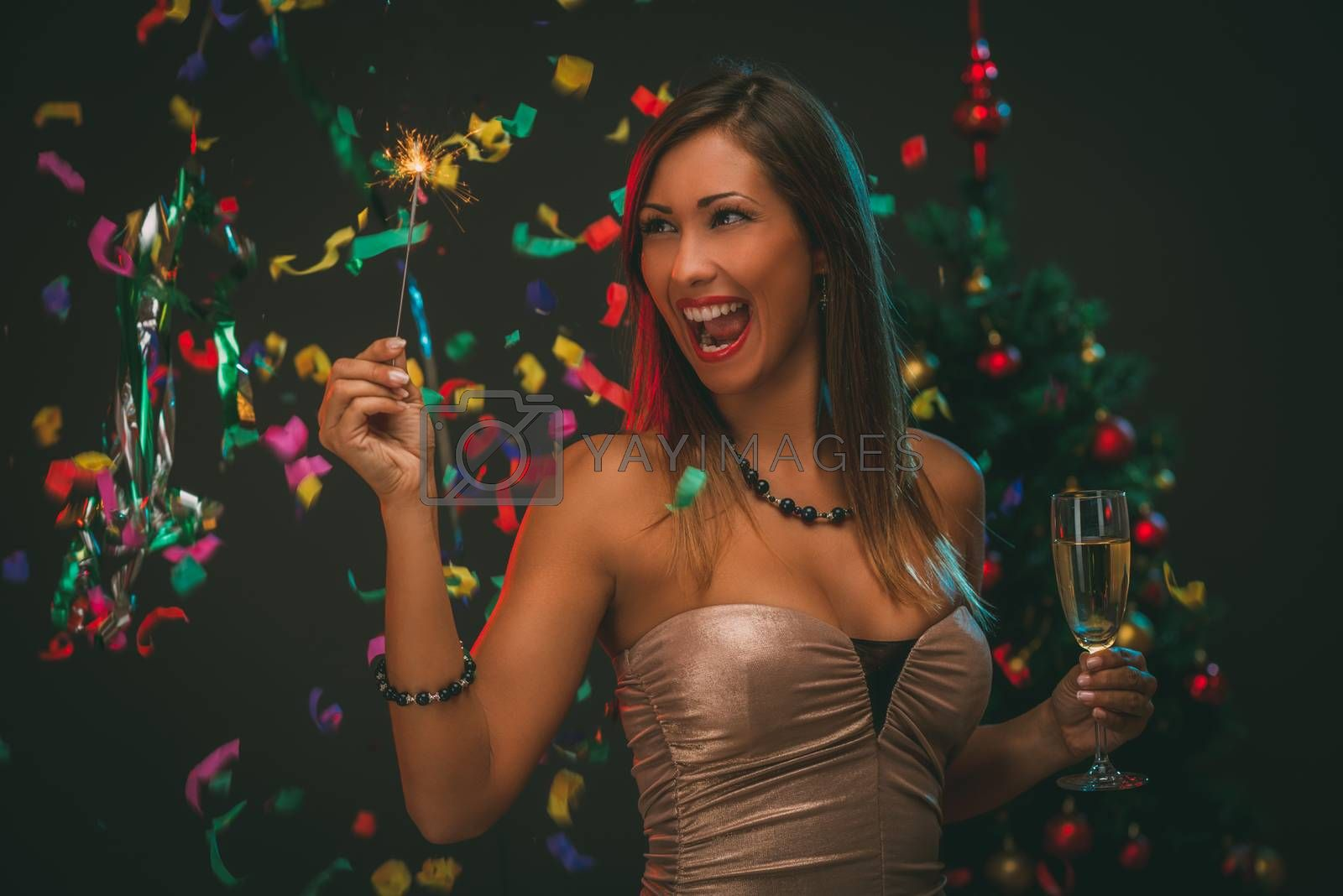 Cheerful beautiful woman celebrating New Year. She is having fun with sparkler and champagne.