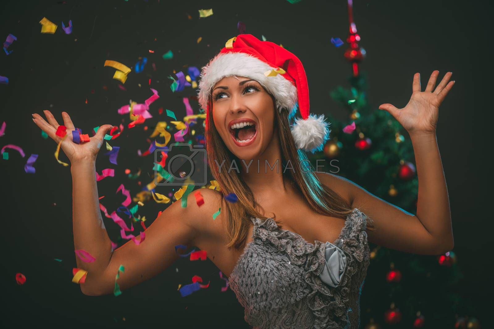 Cheerful beautiful woman celebrating New Year. She is having fun, confetti is the air.