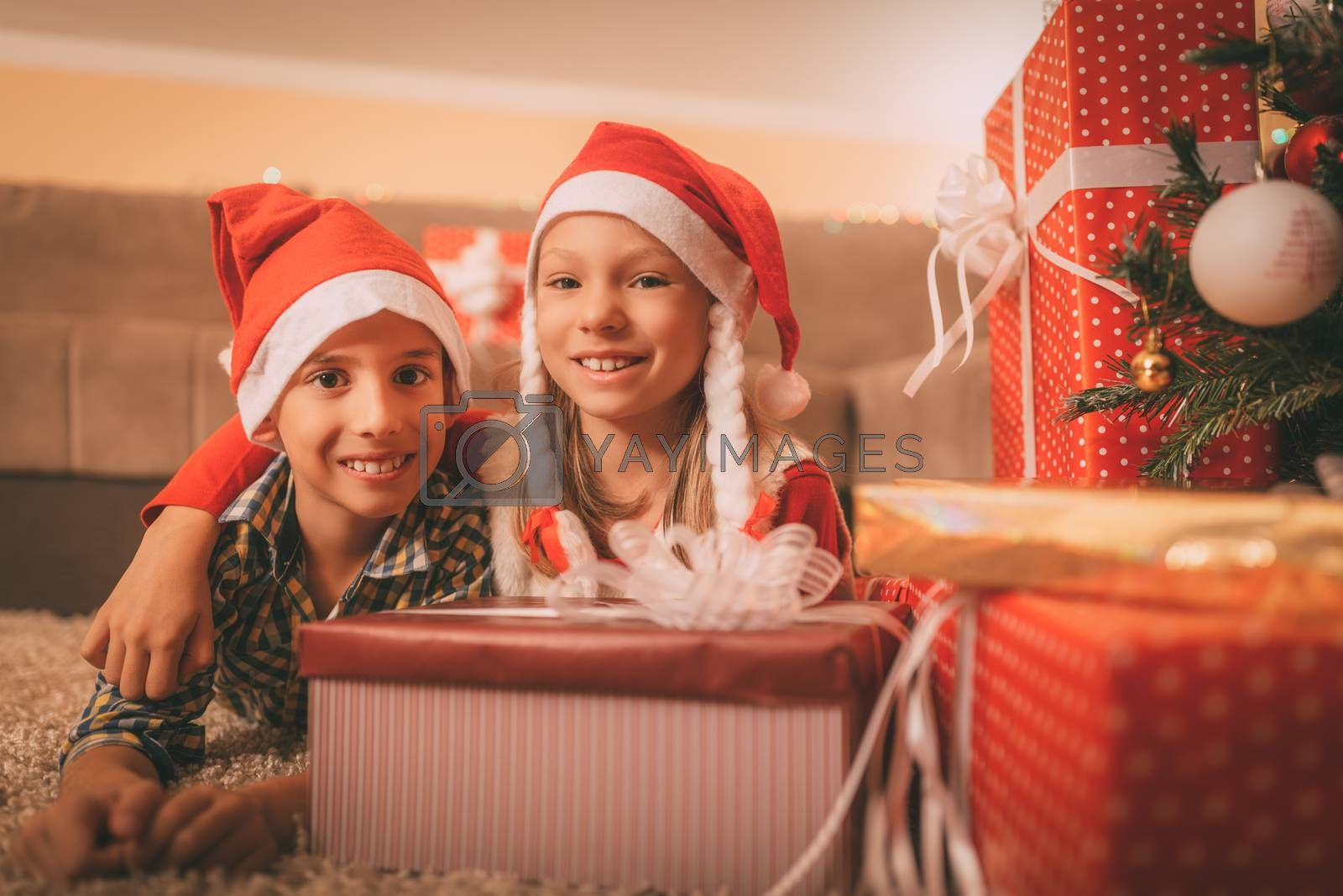 Cute smiling sister and brother with many presents at the home in a Christmas time. They are embraced and looking at camera.