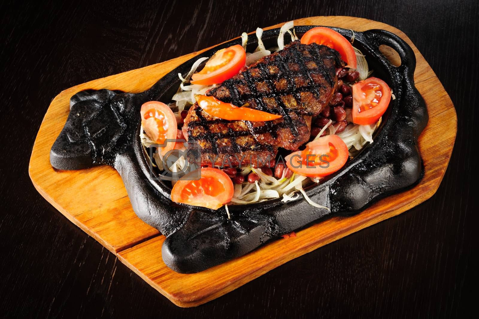 Juicy beef steak with red beans garnish and sliced tomato in cast iron plate