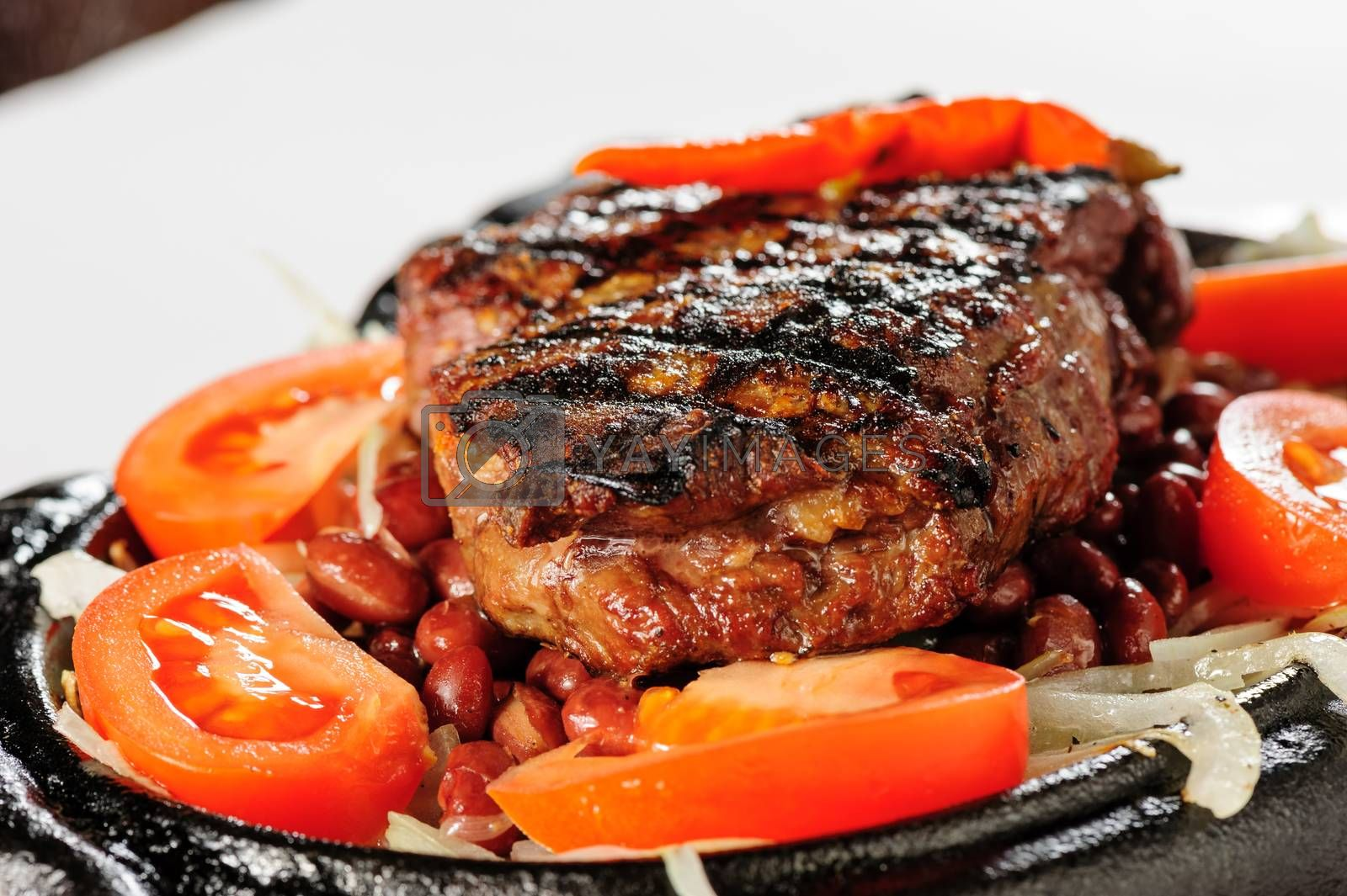 Juicy beef steak with red beans garnish and sliced tomato