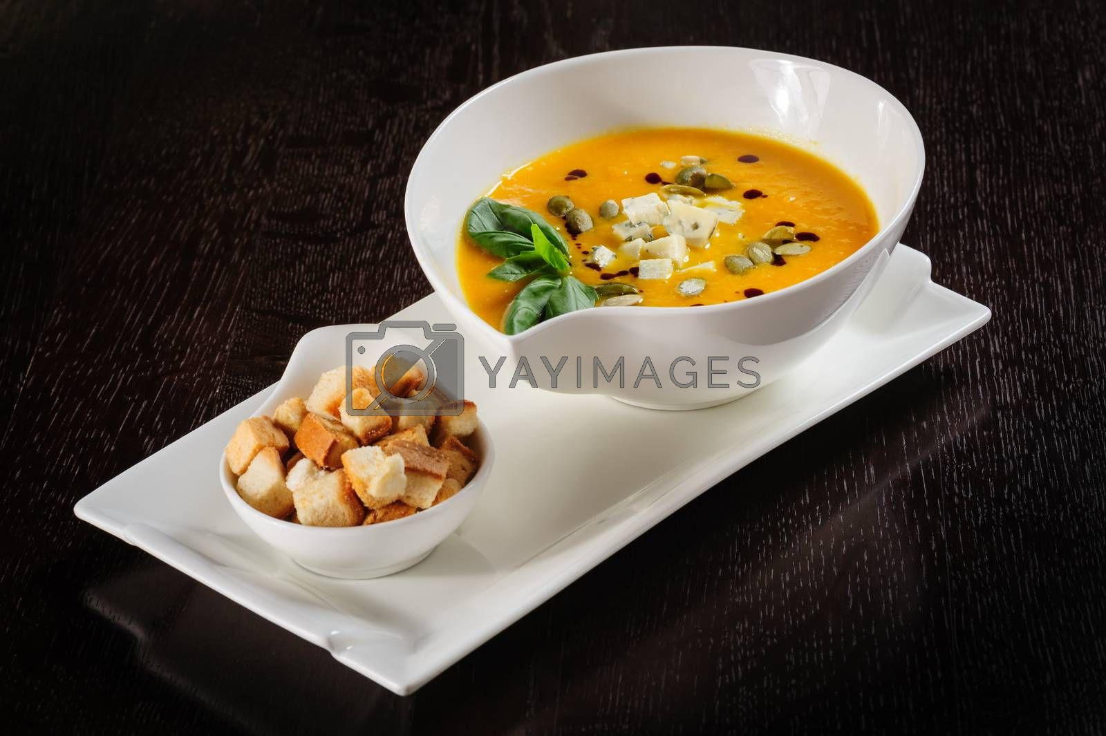 Roasted pumpkin soup with croutons on white background. Copy space.