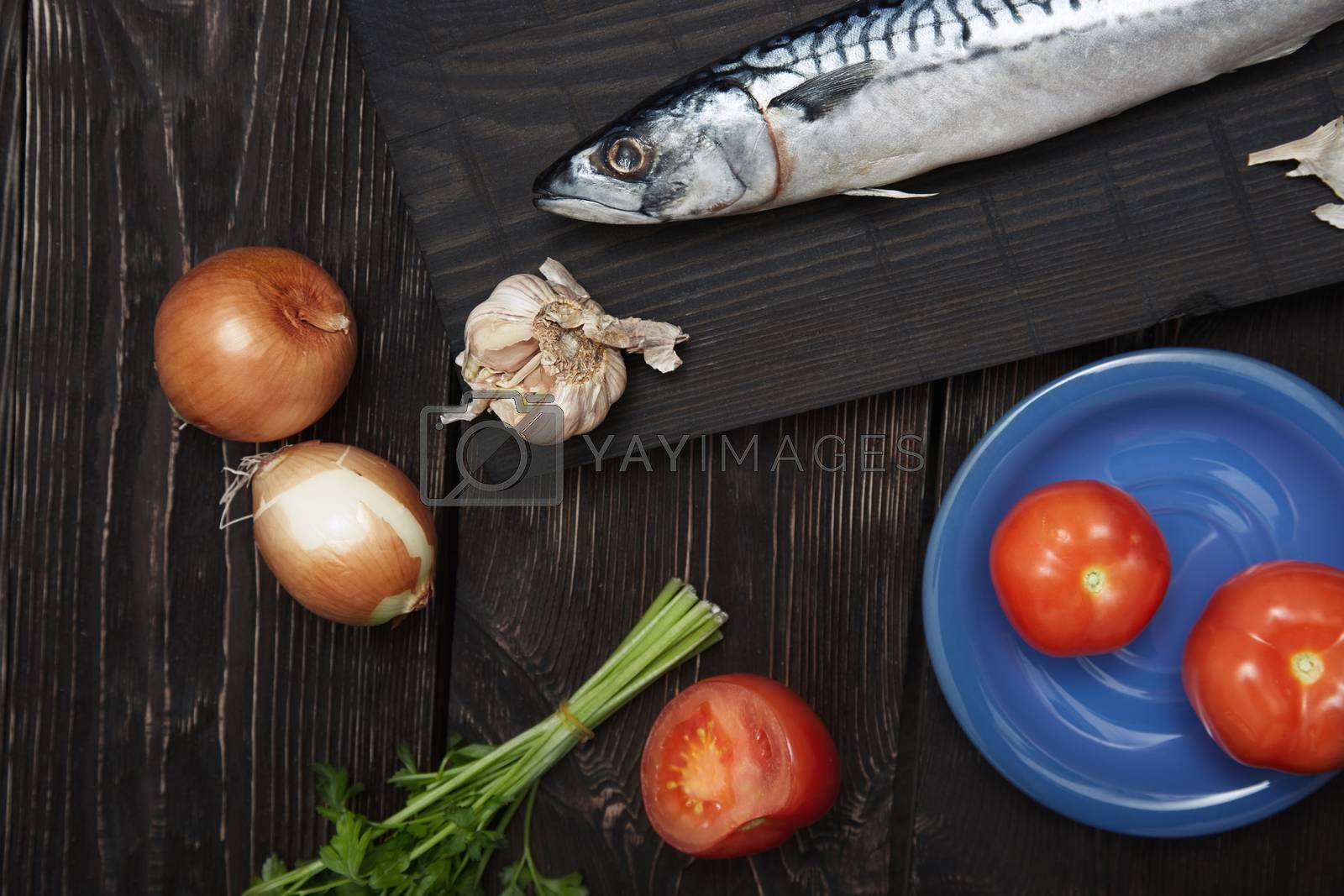 Mackerel and vegetables on a wooden table. Horizonal photo