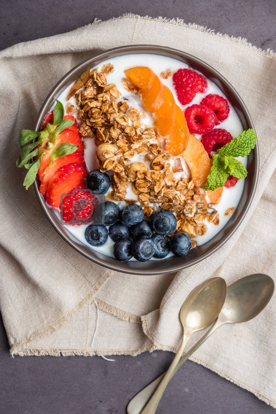 Yogurt with baked granola and berries in small bowl strawberries blueberries. Granola baked with nuts and honey for little sweetness.