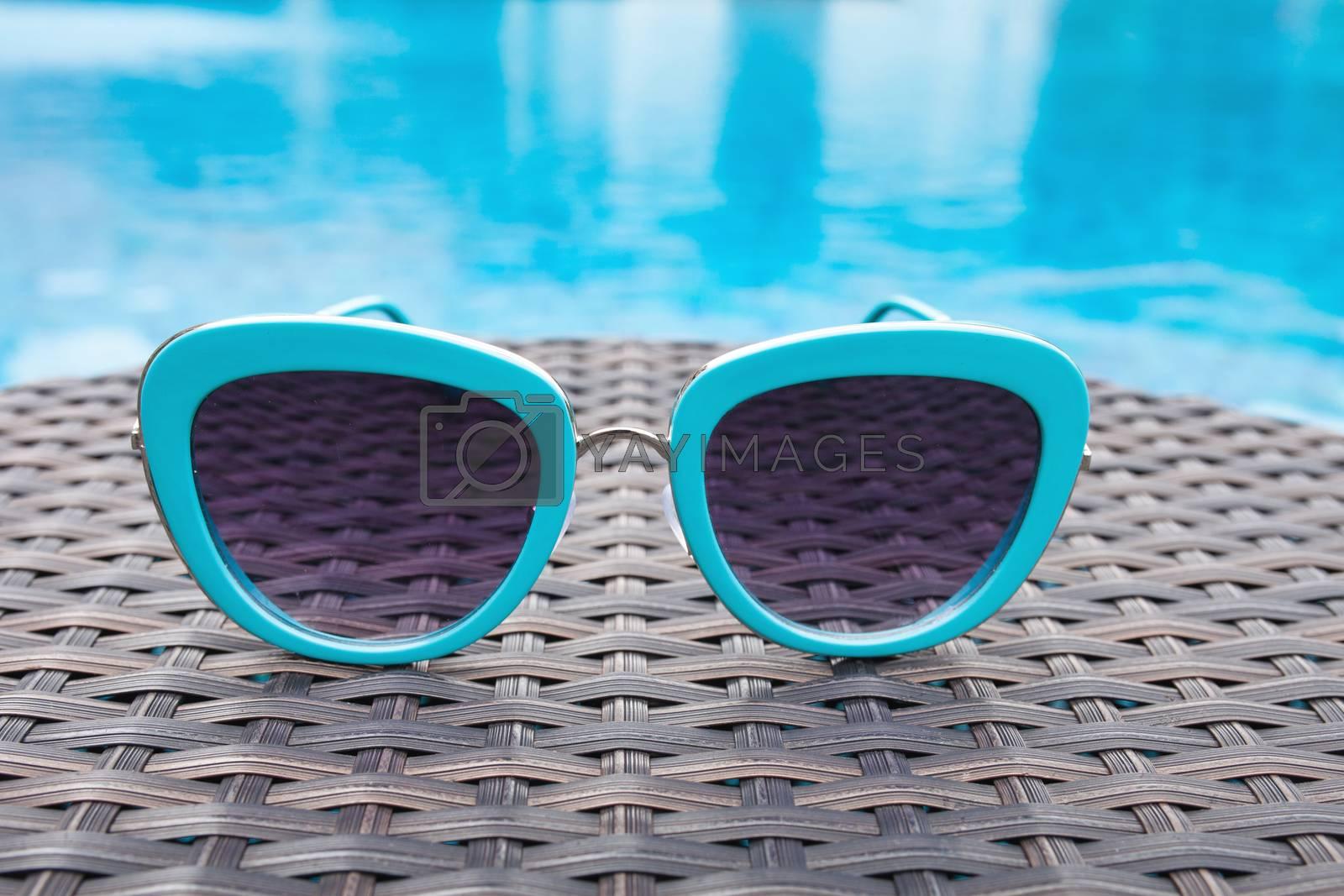 Summertime sunglasses relax near swimming pool.