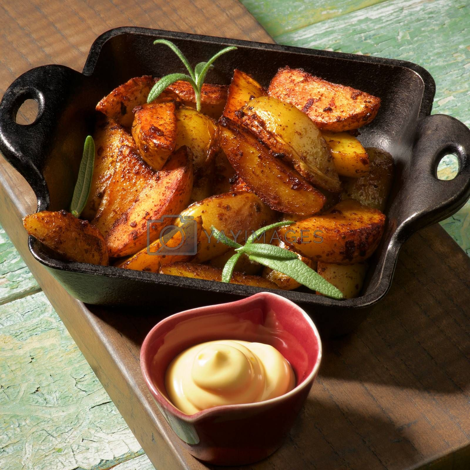Hot Snack with Delicious Roasted Potato Wedges in Black Cast-Iron Pan and Cheese Sauce on Wooden Board closeup in Shadow