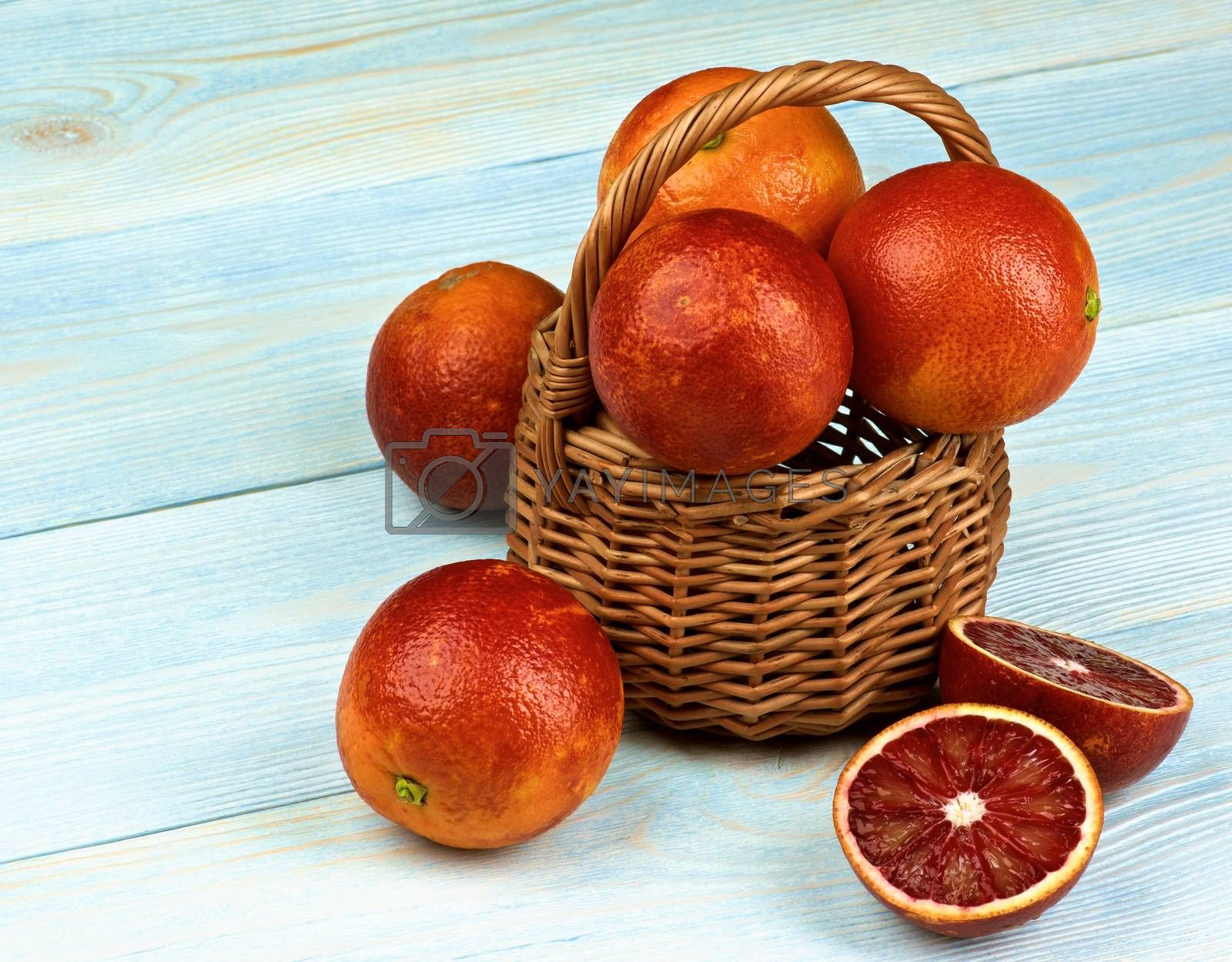 Arrangement of Blood Oranges Full Body and Halves in Wicker Basket closeup on Blue Wooden background