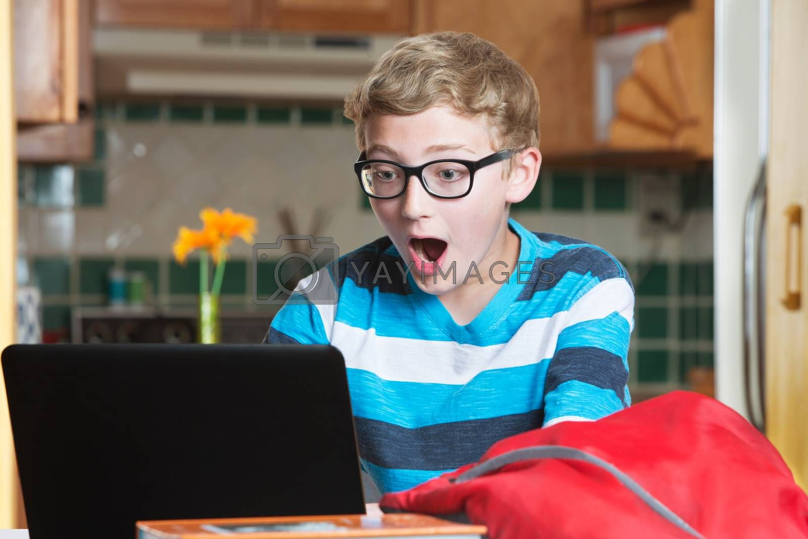 Surprised boy in eyeglasses and striped shirt using laptop with red backpack
