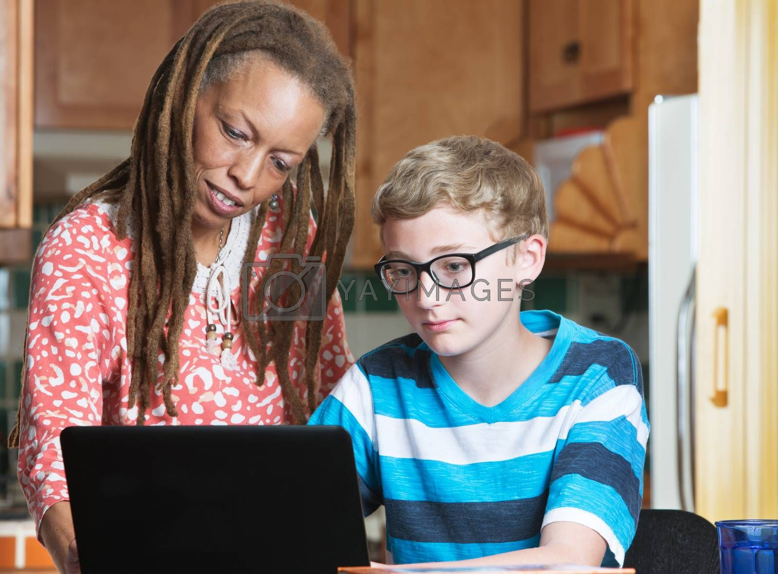 Foster parent helping child in eyeglasses working on laptop