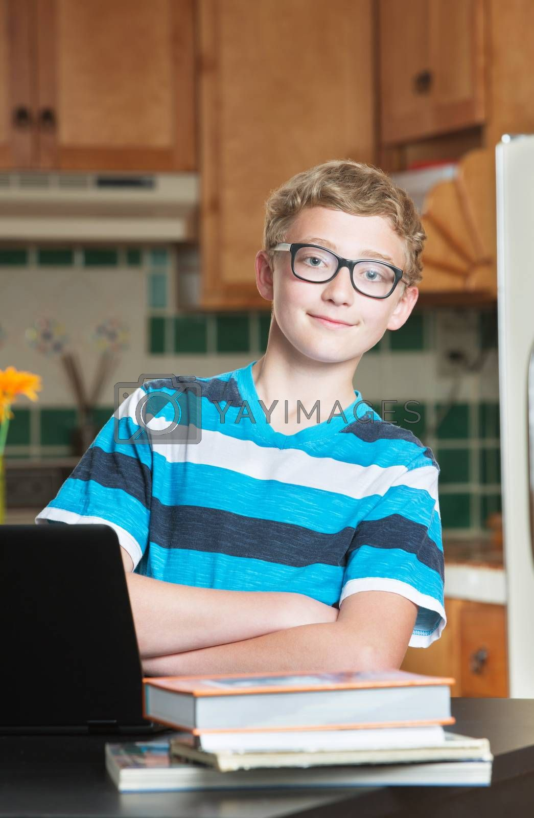 Single confident teenage male student in kitchen with textbooks