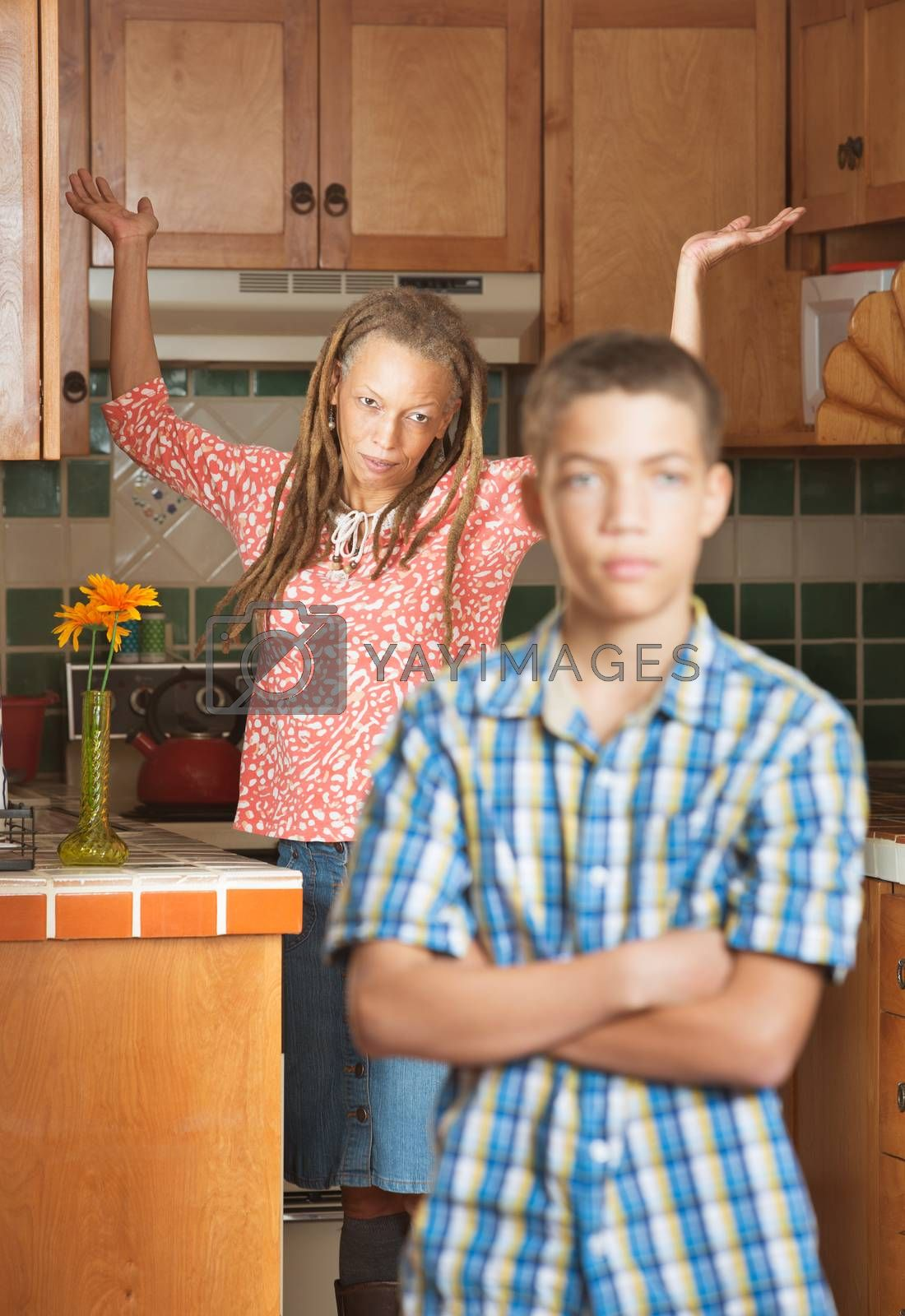 Mother of teenaged son throws her hands up in frustration as they both stand in the kitchen