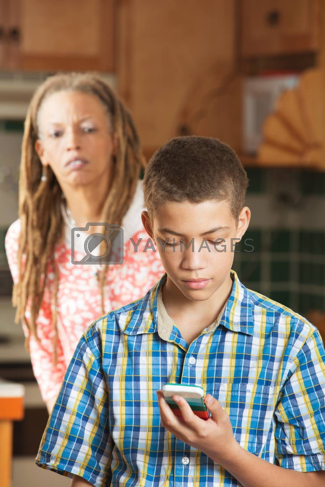 Concerned mother attempts to spy over shoulder of her teenaged son as her reads message on his mobile phone
