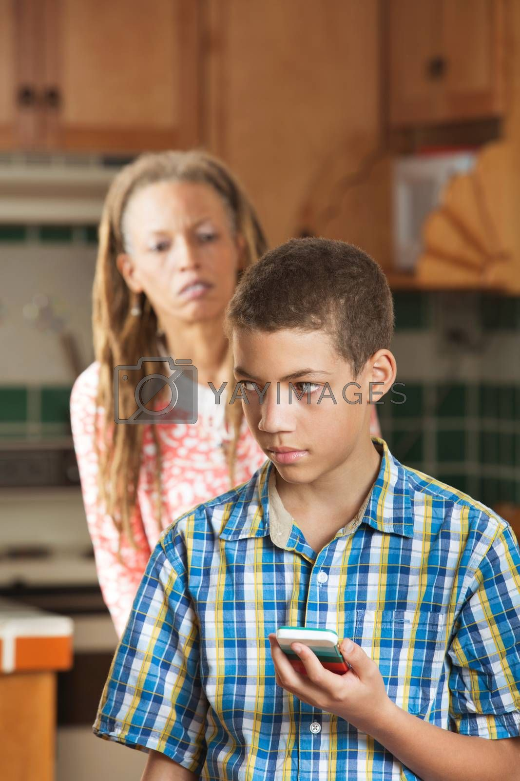 Teenaged son holds cell phone as his curious mother looks questioningly