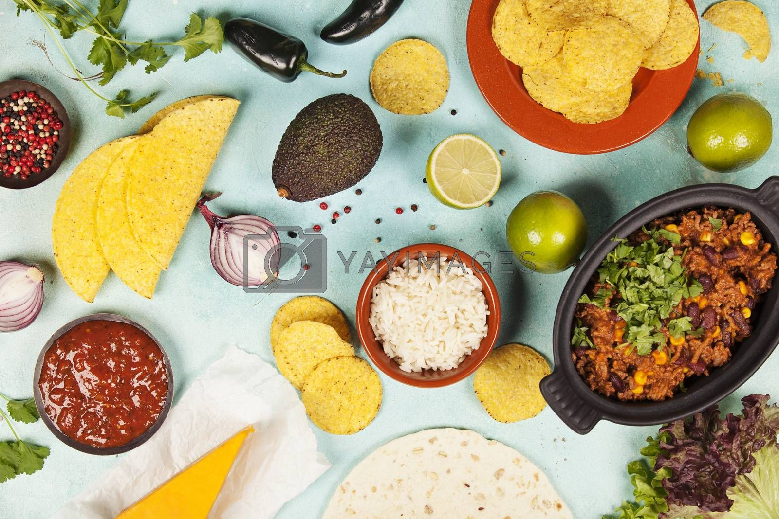 Mexican food concept: tortilla chips, guacamole, salsa, chilli with beans and fresh ingredients over vintage background. Top view