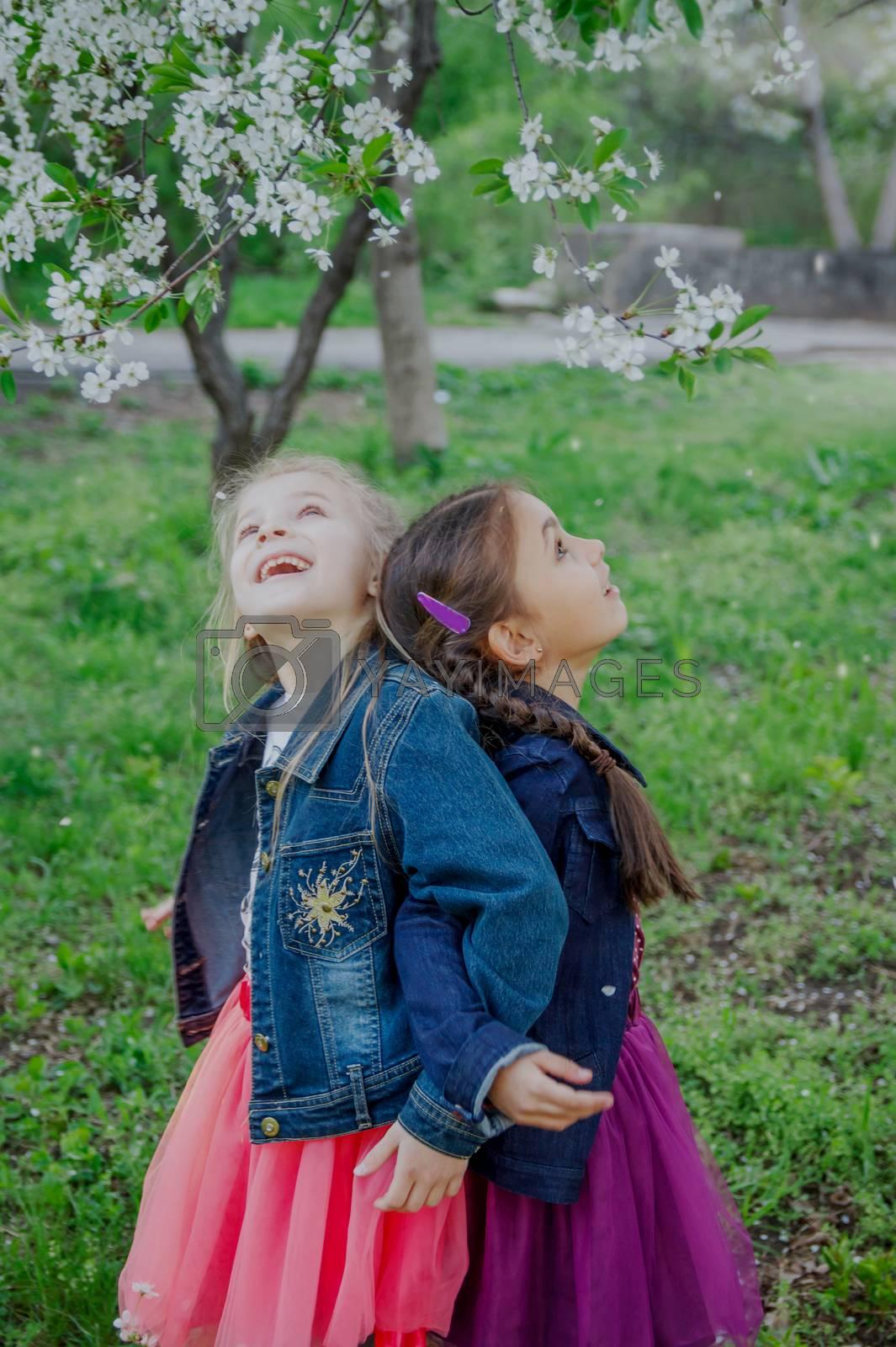 Two happy girls enjoying falling petals in spring garden