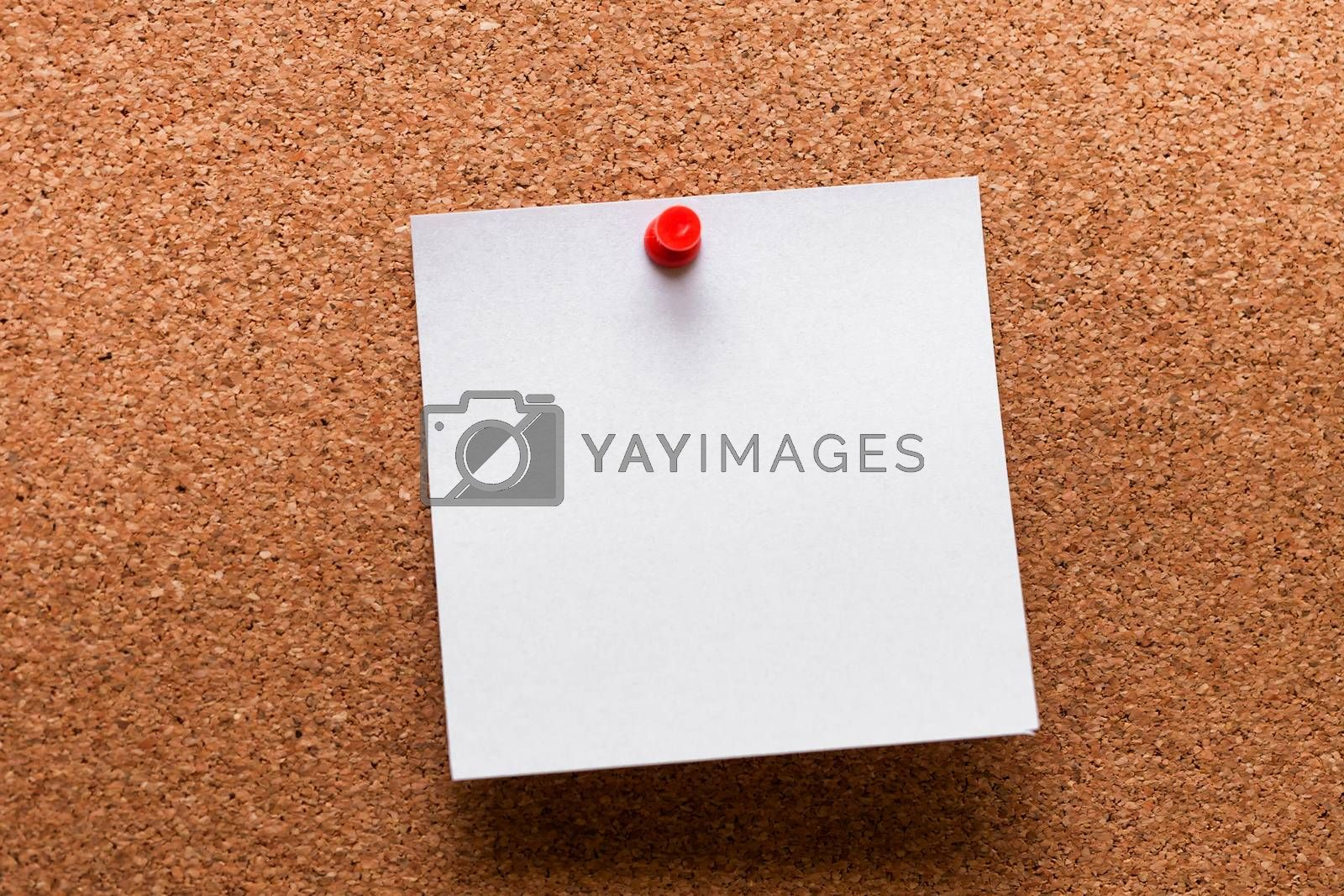 White paper with red clip nailed on wooden board.
