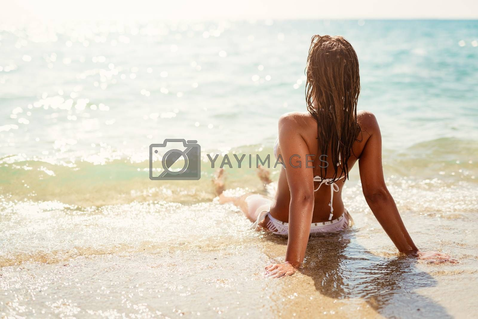 Rear view of a beautiful young woman enjoying on the beach. She is lounging and sunbathing on the sandy coast in the sea.