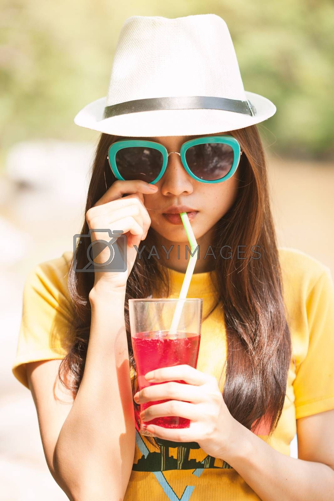 Woman drinking iced drinks outdoors with sand by the sea.