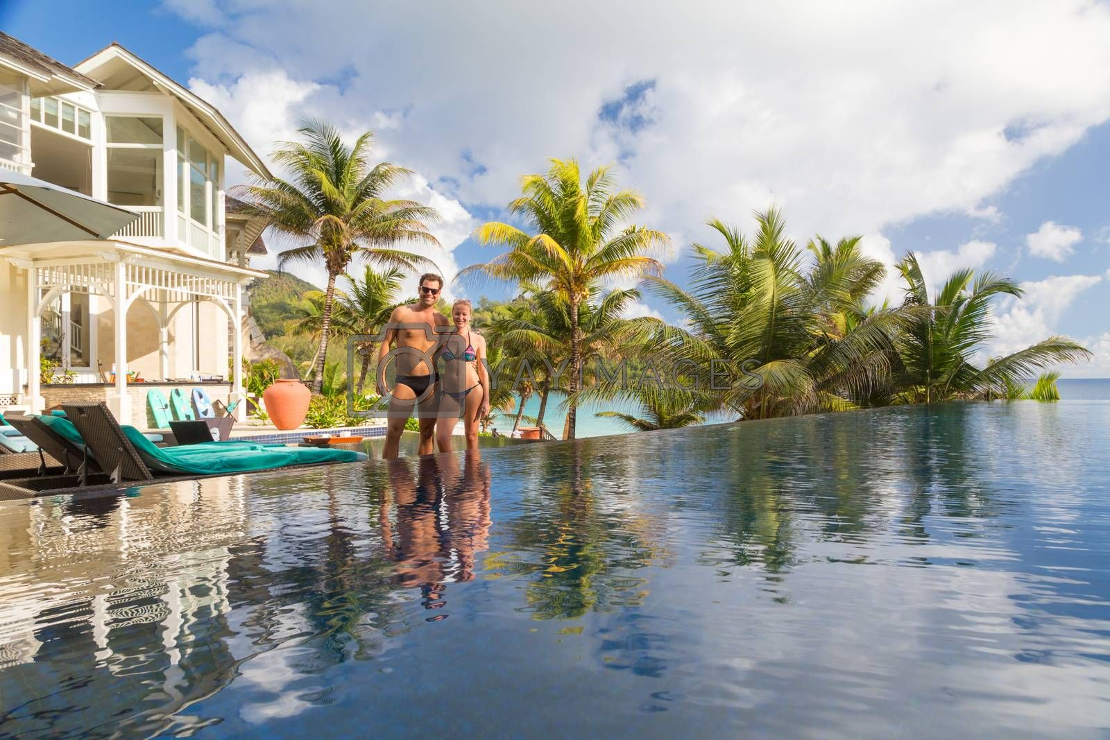 Newlyweds on honeymoon vacations on Mahe island, Seychelles. Couple relaxing by luxury hotel swimming pool surrounded by various type of palm trees on the beach.