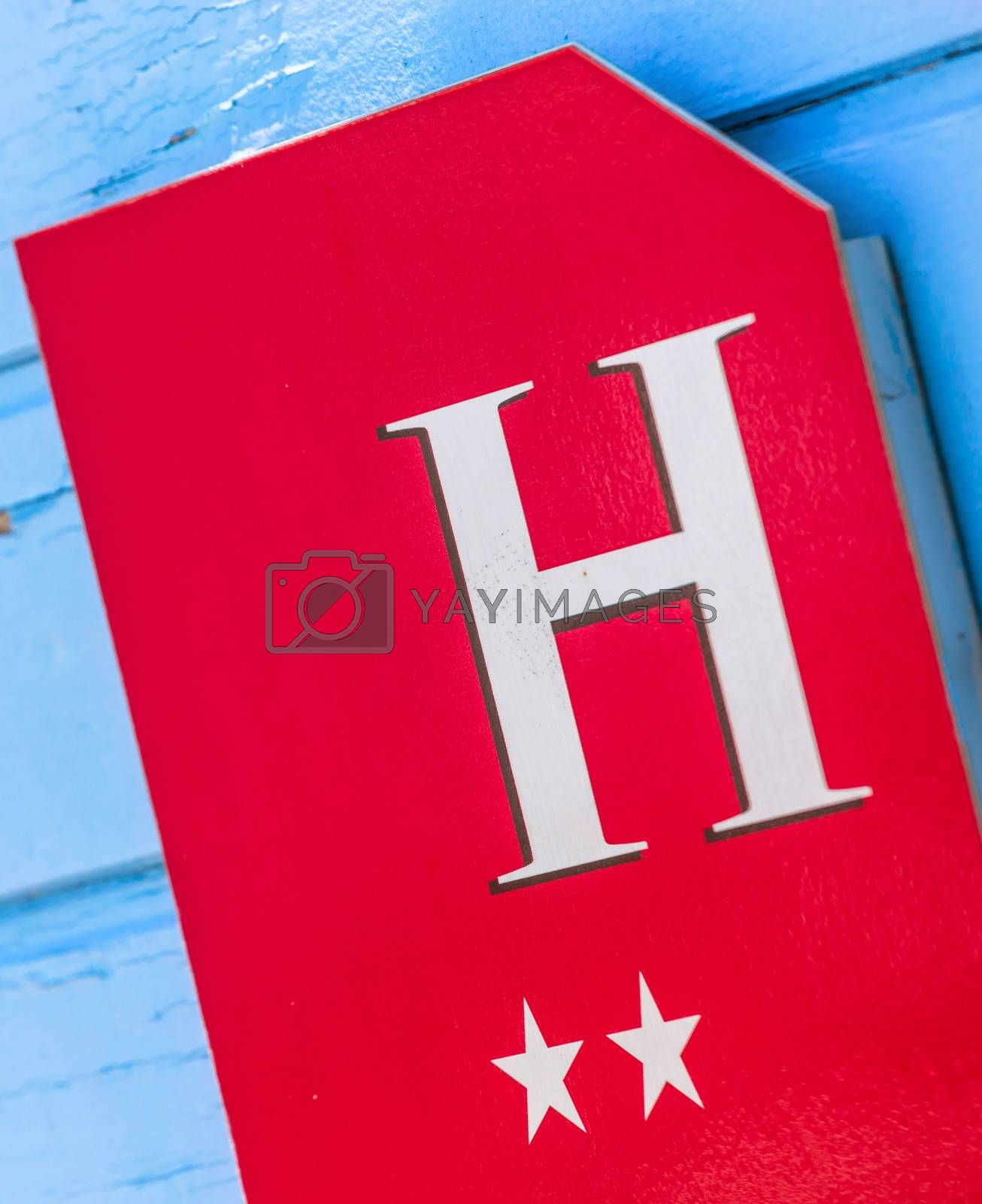 Royalty free image of coloreful hotel sign on wooden wall by pixinoo