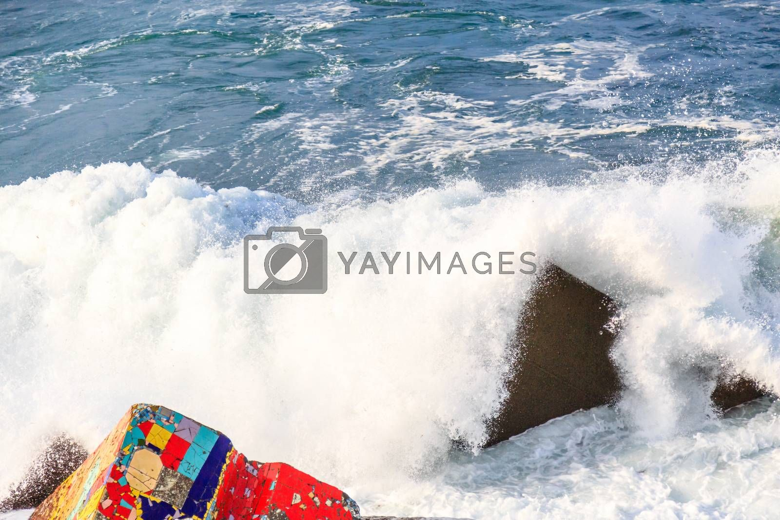 Royalty free image of Seascape with coloreful rocks, foam and spray of the waves by pixinoo