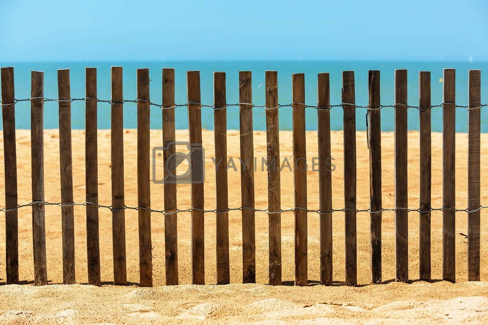 Royalty free image of Palisades on sand beach near ocean. Private beach concept by pixinoo