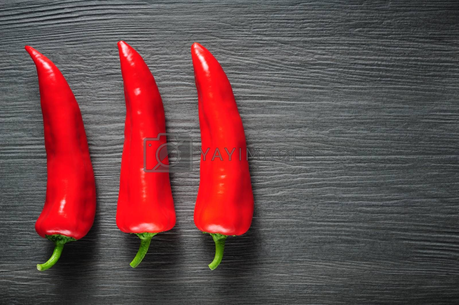 Three ripe sweet red Kapia peppers on dark shale stone background, copy space