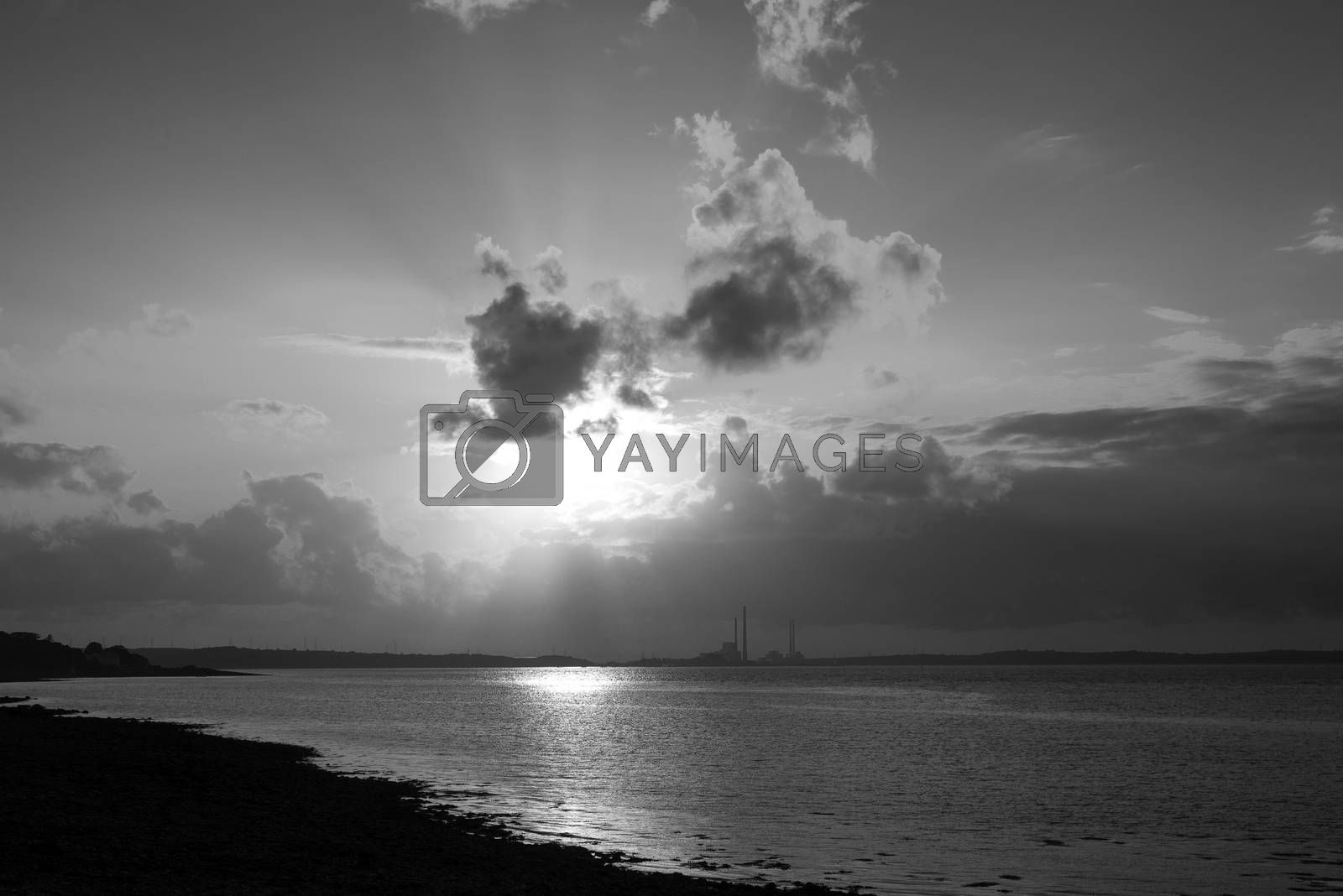 sunset rays over a power station on the river shannon in ireland