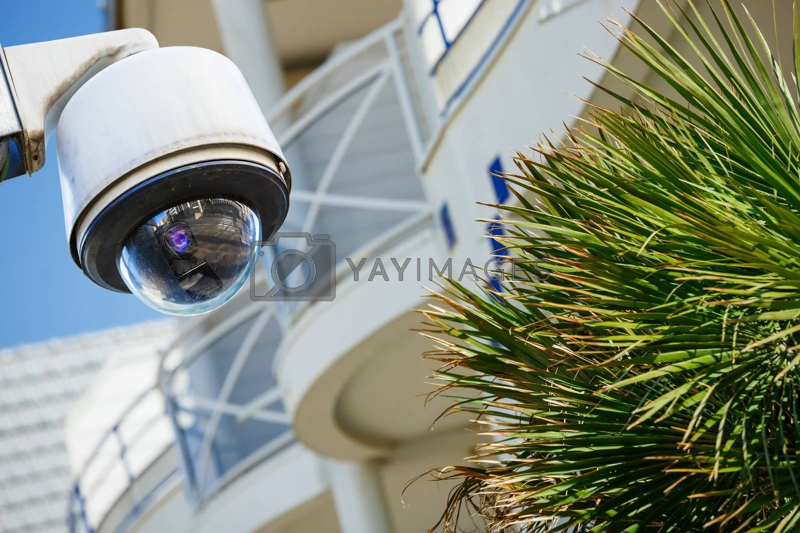 Royalty free image of security CCTV camera or surveillance system with modern luxury residence on blurry background by pixinoo