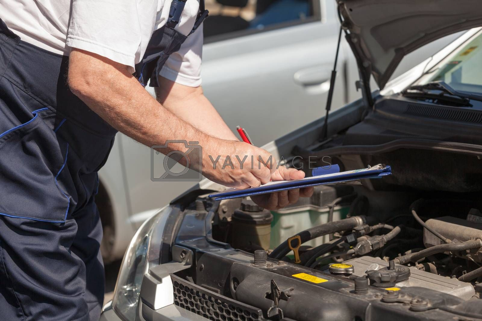 Car or motor mechanic checking a car engine and writing on the clipboard